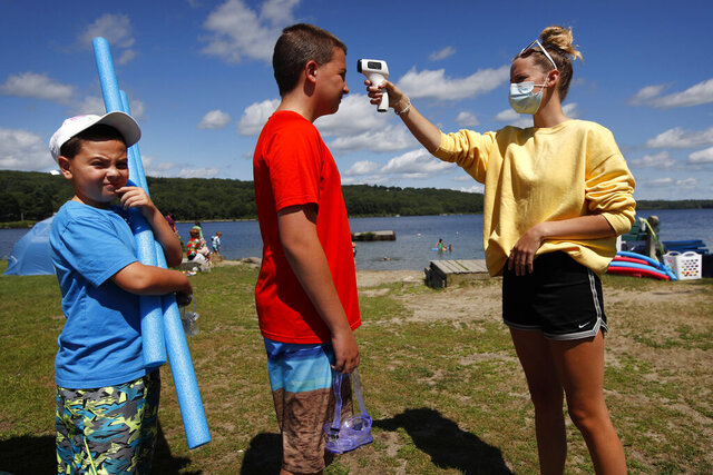 As a precaution to help prevent the spread of coronavirus, beach attendant Danielle McClure takes the temperature of Colten Ryan before allowing him and his brother, Finn, left, to enter Maranacook Beach, Wednesday, Aug. 5, 2020, in Winthrop, Maine. (AP Photo/Robert F. Bukaty)