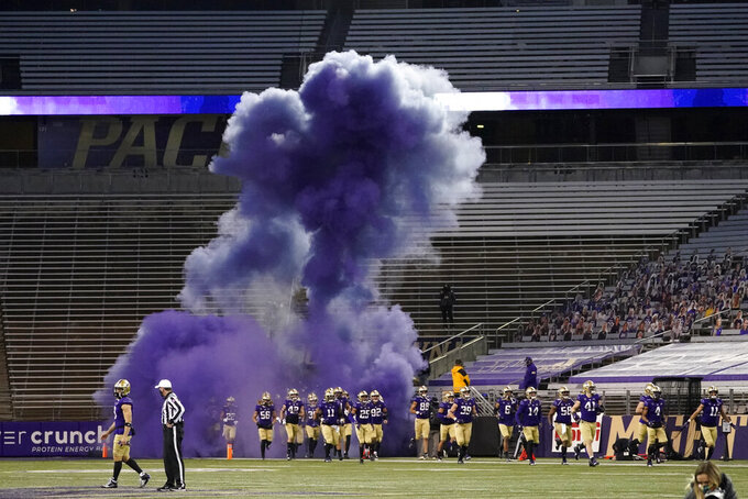 Washington players run out of a tunnel through a cloud of purple smoke in front of empty seats at Husky Stadium before an NCAA college football game against Utah, Saturday, Nov. 28, 2020, in Seattle. Due to the COVID-19 pandemic, no fans were in attendance at the game. (AP Photo/Ted S. Warren)