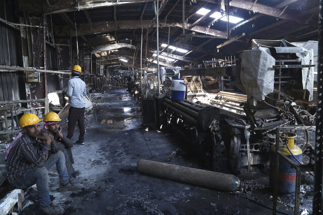 In this Sunday, Feb. 9, 2020 photo, Indian laborers sit near burnt remains after a fire broke out at Nandan Denim, one of the largest denim suppliers in the world, in Ahmedabad, India. At least seven people died in the blaze that swept the factory that has ties to major U.S. retailers, according to its website. Some of the U.S. and multinational companies listed on the website said they were not actually customers, and many issued statements that strongly condemned dangerous work sites. (AP Photo)