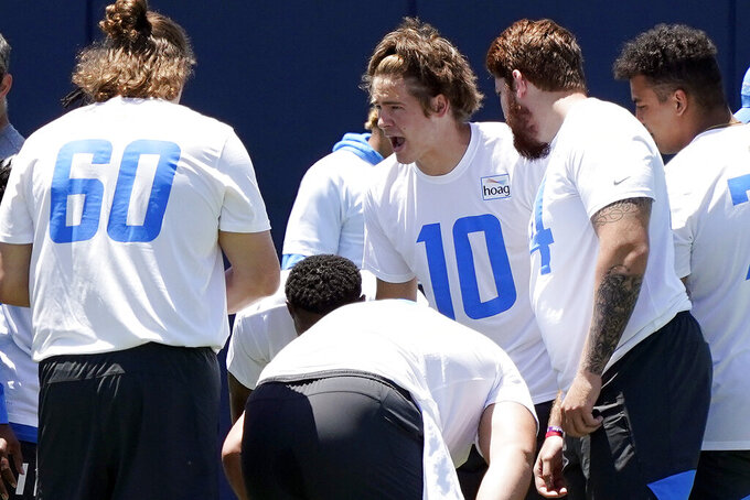 Los Angeles Chargers quarterback Justin Herbert (10) huddles with teammates during the NFL football team's organized team activities Monday, May 24, 2021, in Costa Mesa, Calif. (AP Photo/Marcio Jose Sanchez)