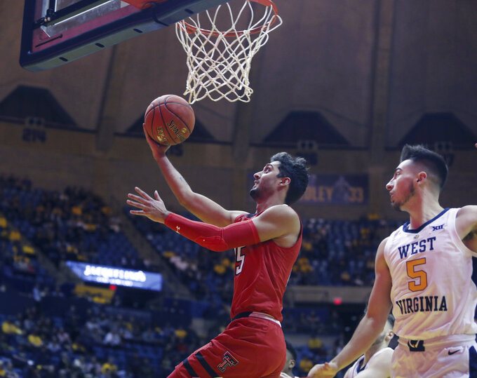 Texas Tech guard Davide Moretti (25) drives while defended by West Virginia guard Jordan McCabe (5) during the first half of an NCAA college basketball game Wednesday, Jan. 2, 2019, in Morgantown, W.Va. (AP Photo/Raymond Thompson)