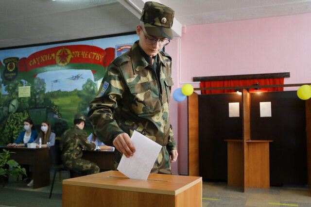 A Belarusian soldier casts his ballot at a polling station during the presidential election in Minsk, Belarus, Sunday, Aug. 9, 2020. After 26 years in office, the authoritarian leader of Belarus is facing the toughest challenge yet as Alexander Lukashenko runs for a sixth term. Discontent over a worsening economy and his government's dismissive response to the coronavirus pandemic has helped fuel the country's largest opposition rallies since he became its first and only elected president following the collapse of the Soviet Union. (AP Photo/Sergei Grits)
