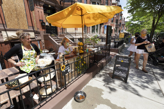 Tracy Casavant, left, owner of Bittersweet Shoppe on Newbury Street, sells lemonade with Cheryl Johnson, Saturday, June 6, 2020, in Boston. Gov. Charlie Baker has announced that retail stores, restaurants and hotels will be allowed to serve customers on Monday as the state mov  es to Phase 2 of reopening businesses that were shut due to concern about COVID-19. (AP Photo/Michael Dwyer)