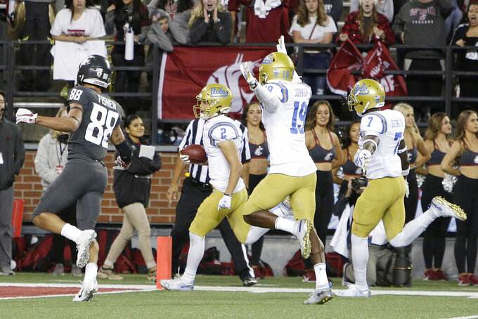 UCLA wide receiver Kyle Philips (2) returns a punt for a touchdown in front of teammates Alex Johnson (19), Mo Osling III (7) and Washington State wide receiver Rodrick Fisher (88) during the second half of an NCAA college football game in Pullman, Wash., Saturday, Sept. 21, 2019. UCLA won 67-63. (AP Photo/Young Kwak)