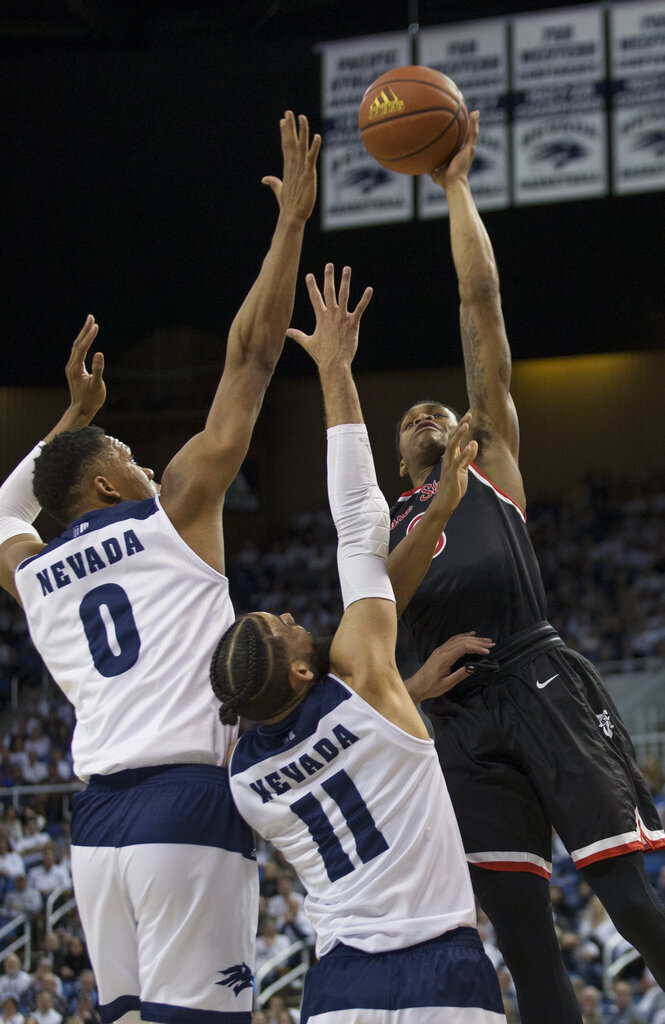 Fresno State guard New Williams (0) shoots over the arms of Nevada forward Tre'Shawn Thurman (0) and forward Cody Martin (11) in the first half of an NCAA college basketball game in Reno, Nev., Saturday, Feb. 23, 2019. (AP Photo/Tom R. Smedes)
