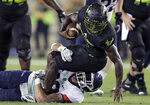 Connecticut linebacker Darrian Beavers, bottom, takes down South Florida running back Jordan Cronkrite after a short gain during the first half of an NCAA college football game Saturday, Oct. 20, 2018, in Tampa, Fla. (AP Photo/Chris O'Meara)