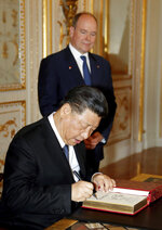 Chinese President Xi Jinping, foreground, signs the register of heads of state as Prince Albert II of Monaco looks on at Monaco Palace, Sunday, March 24, 2019. Xi is paying the first state visit by a Chinese president to the tiny Mediterranean principality of Monaco on Sunday. (Eric Gaillard/Pool Photo via AP)