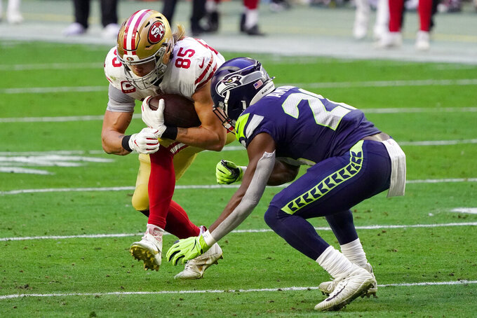 San Francisco 49ers tight end George Kittle (85) is hit by Seattle Seahawks safety Ugo Amadi during the first half of an NFL football game, Sunday, Jan. 3, 2021, in Glendale, Ariz. (AP Photo/Rick Scuteri)