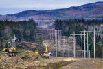 Heavy machinery is used to cut trees to widen an existing Central Maine Power power line corridor to make way for new utility poles, Monday, April 26, 2021, near Bingham, Maine. As President Joe Biden's administration plans to fight climate change by weaning the nation off fossil fuels, these large-scale renewable energy projects are the source of conflict within a seemingly unlikely group: environmentalists. (AP Photo/Robert F. Bukaty)