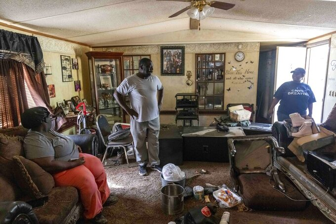 Siblings Candy Roberts, from left, Anthony Roberts and Tyekia Williams talk with one another Sunday, June 20, 2021, in their flood-destroyed home following heavy flooding Saturday, in Northport, Ala. (AP Photo/Vasha Hunt)