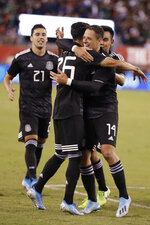 Mexico forward Javier Hernandez (14) embraces midfielder Uriel Antuna (26) after Antuna scored Mexico's third goal, in the second half of an international friendly soccer match against the United States on Friday, Sept. 6, 2019, in East Rutherford, N.J.  Jorge Sanchez is at left. Mexico won 3-0. (AP Photo/Kathy Willens)