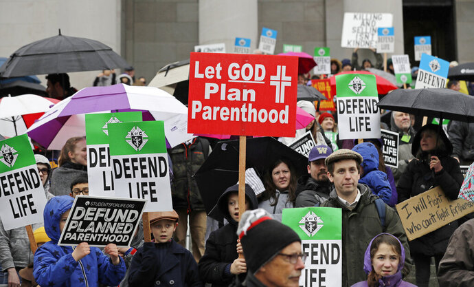 FILE - In this Jan. 22, 2019, file photo, people taking part in an anti-abortion march hold signs as they stand on the steps of the Legislative building at the Capitol in Olympia, Wash. With a flurry of recent actions, Trump's administration is now winning the praise of conservative religious leaders for fulfilling many of their goals opposing abortion and reining in the LGBTQ-rights movement. (AP Photo/Ted S. Warren, File)