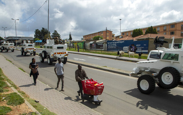 A man pushing a shopping cart with food on the street as South African National Defence Forces drive through a densely populated Alexandra township east of Johannesburg, South Africa, Saturday, March 28, 2020. South Africa went into a nationwide lockdown for 21 days in an effort to control the spread of the COVID-19 coronavirus. The new coronavirus causes mild or moderate symptoms for most people, but for some, especially older adults and people with existing health problems, it can cause more severe illness or death. (AP Photo/Themba Hadebe)