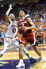 Alabama guard Jaden Shackelford (5) drives past Auburn guard Samir Doughty (10) during the first half of an NCAA college basketball game, Wednesday, Feb. 12, 2020, in Auburn, Ala. (AP Photo/Julie Bennett)