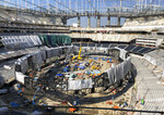 Workers stay busy constructing the interior of SoFi Stadium and preparing to raise the circular Oculus video board in Inglewood, Calif., on Wednesday, Jan. 22, 2020. The estimated $5 billion project is on schedule to open in July as the most expensive stadium in NFL history. (AP Photo/Greg Beacham)