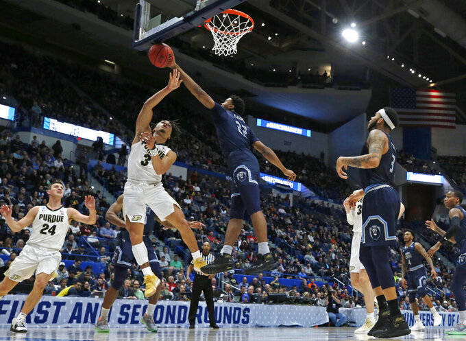 Old Dominion's Kalu Ezikpe (22) blocks a shot by Purdue's Carsen Edwards (3) as Purdue's Grady Eifert (24) and Old Dominion's B.J. Stith (3) look on during the first half of a first-round game in the NCAA men's college basketball tournament Thursday, March 21, 2019, in Hartford, Conn. (AP Photo/Elise Amendola)