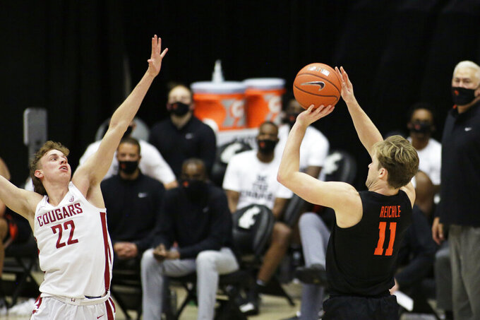 Oregon State guard Zach Reichle (11) shoots over Washington State guard Ryan Rapp (22) during the second half of an NCAA college basketball game in Pullman, Wash., Wednesday, Dec. 2, 2020. Washington State won 59-55. (AP Photo/Young Kwak)