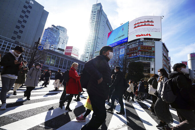 People wearing protective masks to help curb the spread of the coronavirus walk along pedestrian crossings Monday, Jan. 25, 2021 in Tokyo. The Japanese capital confirmed more than 600 new coronavirus cases on Monday. (AP Photo/Eugene Hoshiko)