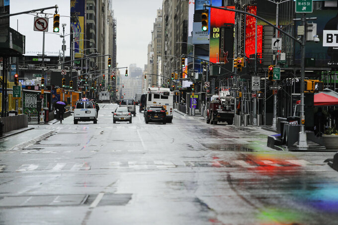 Cars drive down a mostly empty Seventh Avenue during the coronavirus outbreak Friday, April 3, 2020, in New York's Times Square. The new coronavirus causes mild or moderate symptoms for most people, but for some, especially older adults and people with existing health problems, it can cause more severe illness or death. (AP Photo/Frank Franklin II)