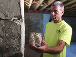 In this  July 1, 2019 photo, contractor Don Childree holds a chunk of concrete pulled from the wall of a crumbling house foundation in Vernon, Conn. The concrete foundation is deteriorating due to the presence of an iron sulfide known as pyrrhotite, often described as