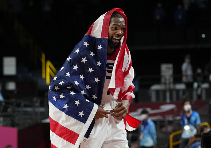 United States' Kevin Durant (7) drapes himself with a United States flag as he celebrates with teammates after their win over France in a men's basketball Gold medal game at the 2020 Summer Olympics, Saturday, Aug. 7, 2021, in Saitama, Japan. (AP Photo/Eric Gay)