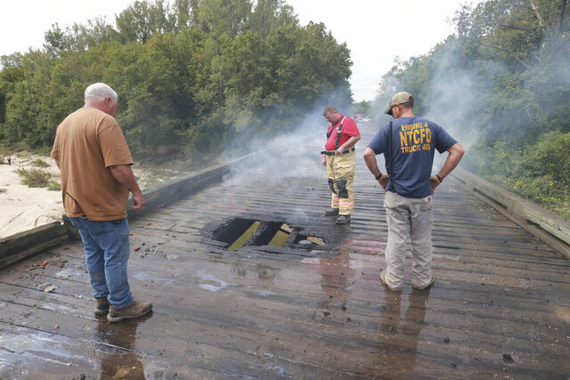 Firefighers inspect the area where the fire started on the wooden decking of a bridge on Lee County Road 1213 near Baldwyn, Miss., that left the bridge destroyed Tuesday, Sept. 22, 2020. Arson is suspected as the cause of the fire. (Thomas Wells/The Northeast Mississippi Daily Journal via AP)