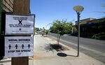 Social distancing signs are posted at one of the bars closed for the next 30 days due to the surge in coronavirus cases Tuesday, June 30, 2020, in Scottsdale, Ariz. (AP Photo/Ross D. Franklin)