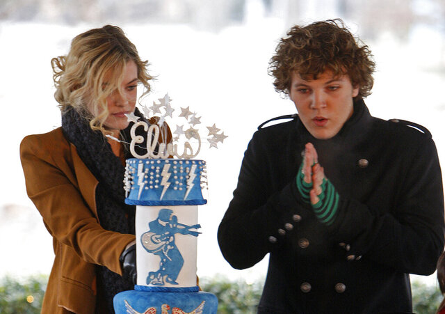 FILE - In this Friday, Jan. 8, 2010, file photo, Riley Keough, 21, left, cuts the birthday cake as her brother, Benjamin, 18, right, warms his hands as they take part in a ceremony commemorating Elvis Presley's 75th birthday in Memphis, Tenn. Both are the children of Lisa Marie Presley and the grandchildren of Elvis Presley. Officials said Wednesday, Oct. 7, 2020, that Benjamin Storm Presley Keough   has been buried alongside his relatives at Graceland in Memphis. Keough died in California in July at age 27. (AP Photo/Mark Humphrey, File)