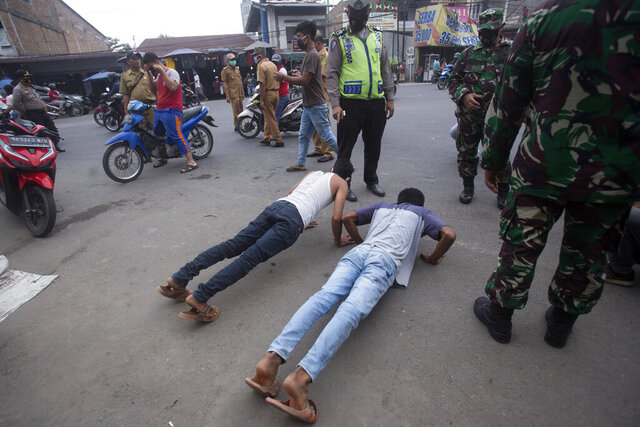 An Indonesian policeman and soldiers watch men do push-ups as a punishment for violating city regulation requiring people to wear face masks in public places as a precaution against coronavirus outbreak, in Medan, North Sumatra, Indonesia, Wednesday, Sept. 23, 2020. (AP Photo/Binsar Bakkara)