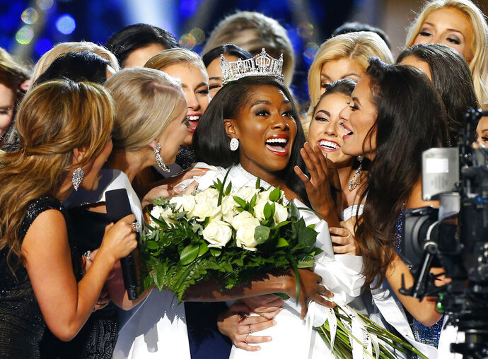 FILE - This Sept. 9, 2018 file photo shows Miss New York Nia Franklin, center, reacting after being named Miss America 2019 in Atlantic City, N.J. The Miss America Organization has denied credentials to cover this year's pageant to several media outlets including its traditional hometown newspaper. The Press of Atlantic City, Washington Post and a magazine that covers the pageant have all been told they will not receive press credentials, but were not told why. (AP Photo/Noah K. Murray, File)