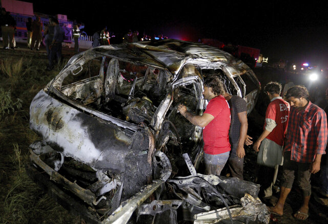 Rescue workers examine a burnt van at the accident site on a highway about 50 kilometers (31 miles) outside of Karachi, Pakistan, Saturday, Sept. 26, 2020. A passenger van overturned and caught fire on a highway in southern Pakistan killed and injured some people, local media reported. (AP Photo/Fareed Khan)