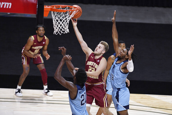Boston College's Rich Kelly, center, goes up for a basket as Rhode Island's Makhi Mitchell, left, and Malik Martin defend during the second half of an NCAA college basketball game Thursday, Nov. 26, 2020, in Uncasville, Conn. (AP Photo/Jessica Hill)