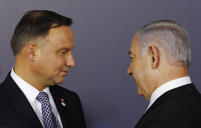 FILE - In this Wednesday, Feb. 13, 2019 file photo, Polish President Andrzej Duda , left, and Israeli Prime Minister Benjamin Netanyahu, talk after a group photo during a two-day international conference on the Middle East, at the Royal Castle in Warsaw, Poland. An off-hand comment by Netanyahu in Warsaw about Poland and the Holocaust looks to overshadow a summit of central European leaders this week in Israel. Poland's abrupt decision Sunday to downgrade its participation in the Visegrad conference suddenly cast a pall gathering. (AP Photo/Czarek Sokolowski, File)