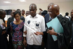 Accompanied by his wife and his lawyers, Congo opposition candidate Martin Fayulu, right, petitions the constitutional court following his loss in the presidential elections in Kinshasa, Congo, Saturday Jan. 12, 2019. The ruling coalition of Congo's outgoing President Joseph Kabila has won a large majority of national assembly seats, the electoral commission announced Saturday, while the presidential election runner-up was poised to file a court challenge alleging fraud. (AP Photo/Jerome Delay)