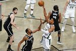Milwaukee Bucks' Giannis Antetokounmpo (34) shoots over Brooklyn Nets' Kevin Durant (7) during overtime of Game 7 of a second-round NBA basketball playoff series Saturday, June 19, 2021, in New York. (AP Photo/Frank Franklin II)
