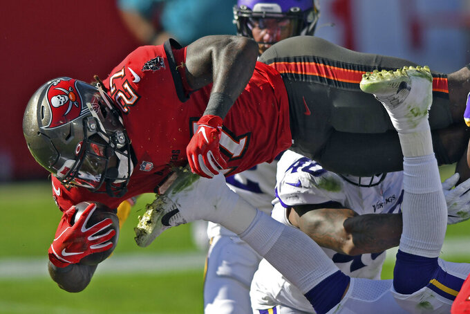 Tampa Bay Buccaneers running back Ronald Jones II (27) dives over the line to score on a 1-yard touchdown run against the Minnesota Vikings during the first half of an NFL football game Sunday, Dec. 13, 2020, in Tampa, Fla. (AP Photo/Jason Behnken)