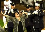 """FILE - In this Sept. 21, 2001, file photo, Liza Minnelli belts out """"New York, New York"""" during the seventh inning stretch as New York City policemen and firemen cheer her on during the New York Mets' baseball game against the Atlanta Braves at Shea Stadium In New York. (AP Photo/Bill Kostroun, File)"""