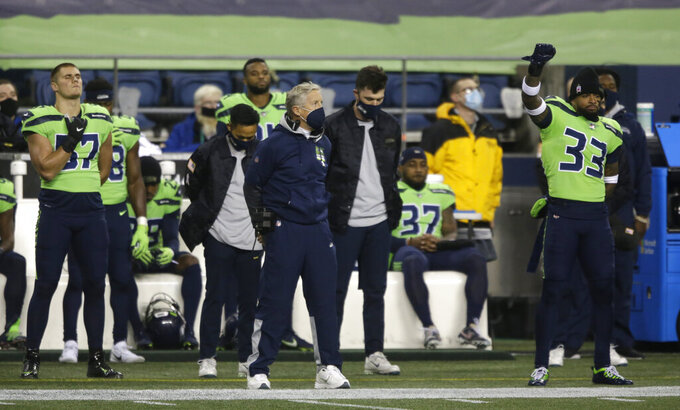 Seattle Seahawks head coach Pete Carroll, center, stands during the national anthem as strong safety Jamal Adams (33) raises his fist and other players sit on the bench in support of Black Lives Matter before an NFL football game against the Arizona Cardinals, Thursday, Nov. 19, 2020, in Seattle. (AP Photo/Lindsey Wasson)
