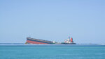 The MV Wakashio, a bulk carrier ship that recently ran aground off the southeast coast of Mauritius, can bee seen from the coast or Mauritius, Wednesday Aug. 12, 2020. Anxious residents of this Indian Ocean island nation have stuffed fabric sacks with sugar cane leaves in an effort to stop the oil spill from reaching their shores. (AP Photo/ Kooghen Modeliar-Vyapooree-L'express Maurice)