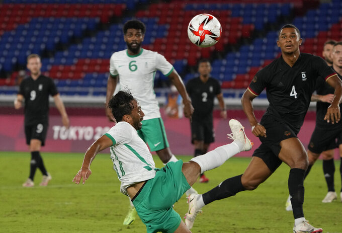 Saudi Arabia's Khalid Alghannam strikes the ball as Germany's Felix Uduokhai, right, defends during a men's soccer match at the 2020 Summer Olympics, Sunday, July 25, 2021, in Yokohama, Japan. (AP Photo/Kiichiro Sato)