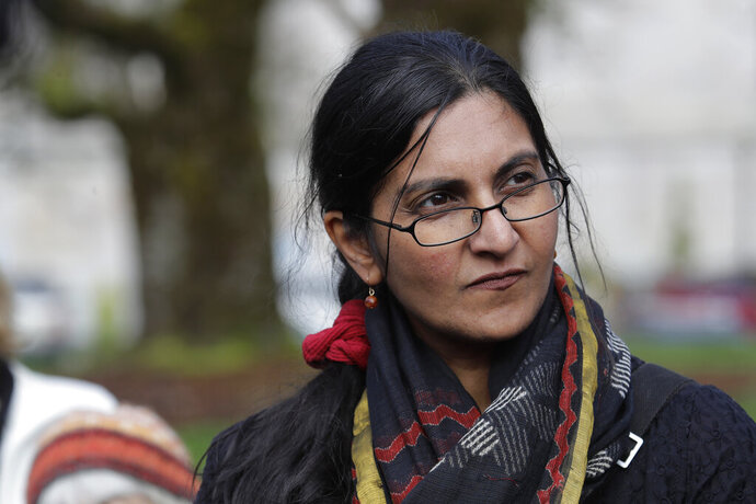 Seattle city councilmember Kshama Sawant listens as she appears at a rally in support of her proposal for a tax on large businesses that she says would raise $300 million to build thousands of new homes in Seattle and retrofit existing homes, Wednesday, Feb. 12, 2020, at the Capitol in Olympia, Wash. Sawant said her plan would direct 75% of the money raised by the tax to build affordable housing and 25% to convert Seattle homes from gas and oil to electric systems. (AP Photo/Ted S. Warren)