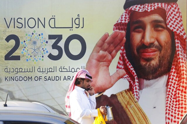 In this Wednesday, Feb. 5, 2020, photo, a Saudi man carries his coffee pot as he walks past a banner showing Saudi Crown Prince Mohammed bin Salman, outside a mall in Jiddah, Saudi Arabia. Human rights organization Amnesty International says Saudi Arabia has used a special anti-terrorism court as