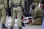 A medic provides care to a woman lying on the ground near police officers, as one of them tries to help her during an opposition rally to protest the official presidential election results in Minsk, Belarus, Saturday, Sept. 19, 2020. Daily protests calling for the authoritarian president's resignation are now in their second month and opposition determination appears strong despite the detention of protest leaders. (AP Photo/TUT.by)