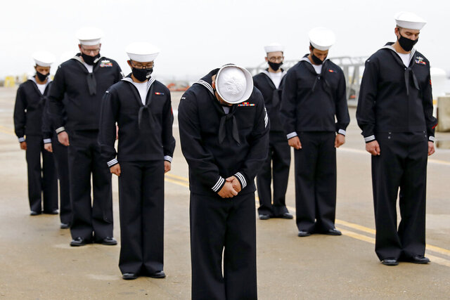 Sailors of the USS Cole bow their heads during a benediction following a remembrance ceremony commemorating the 20th anniversary of the attack on USS Cole at Naval Station Norfolk on Monday, Oct. 12, 2020. (Jonathon Gruenke/The Virginian-Pilot via AP)