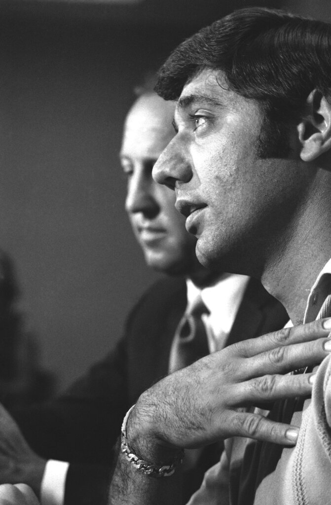 FILE - In this July 18, 1969, file photo, New York Jets quarterback Joe Namath speaks during a press conference as football commissionr Pete Rozelle, rear, looks on, in New York.  Rozelle announced that Namath has decided to sell his half-interest in a New York City nightclub, Bachelors III.  The fear was always that the public wouldn't believe the games were legitimate if there was any hint of scandal. That's why Paul Hornung and Alex Karras were suspended for a year in 1963 for betting a few hundred dollars on games other teams were playing. It's why Joe Namath was forced to sell his New York nightclub in 1969 after NFL investigators determined illegal bookies were hanging out there.(AP Photo/Ron Frehm, File)