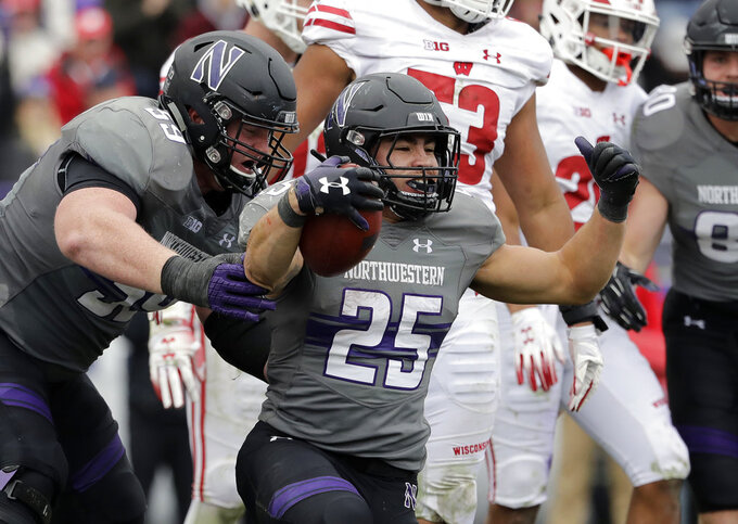 Northwestern running back Isaiah Bowser (25) celebrates with J.B. Butler after scoring a touchdown against Wisconsin during the second half of an NCAA college football game in Evanston, Ill., Saturday, Oct. 27, 2018. Northwestern won 31-17. (AP Photo/Nam Y. Huh)