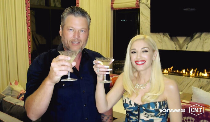 """In this video image provided by CMT, Blake Shelton, left, and Gwen Stefani  toast as they accept the collaboration of the year award for """"Nobody But You"""" during the Country Music Television awards airing on Wednesday, Oct. 21, 2020. (CMT via AP)"""