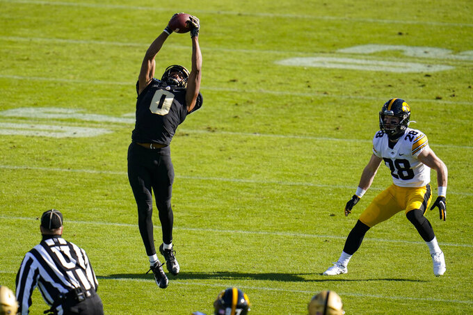 Purdue wide receiver Milton Wright (0) makes a catch in front of Iowa defensive back Jack Koerner (28) during the first quarter of an NCAA college football game in West Lafayette, Ind., Saturday, Oct. 24, 2020. (AP Photo/Michael Conroy)