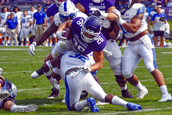 Northwestern running back Evan Hull scores a touchdown against Indiana State defensive back Ty Hambright (32) during the first half of an NCAA college football game in Evanston, Ill, Saturday, Sept. 11, 2021. (AP Photo/Matt Marton)