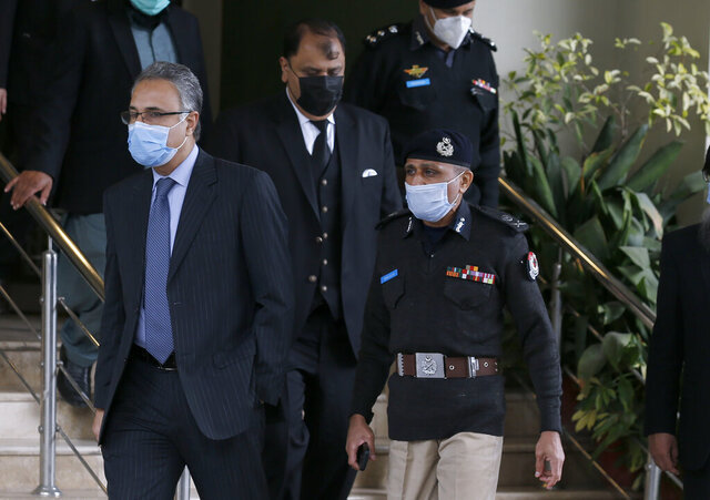 Sanaullah Abbasi, right, Police chief of Pakistan's Khybder Paktunkhwa province and other provincial officials leave the Supreme Court after a hearing in the case of a Hindu temple that was vandalized, in Islamabad, Pakistan, Tuesday, Jan. 5, 2021. Pakistan's Supreme Court ordered authorities Tuesday to rebuild a century-old Hindu temple that was vandalized and set on fire by a mob last week, drawing condemnation from the government and leaders of minority Hindus. (AP Photo/Anjum Naveed)